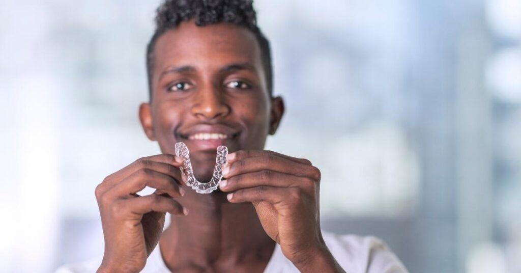 black man hold invisalign