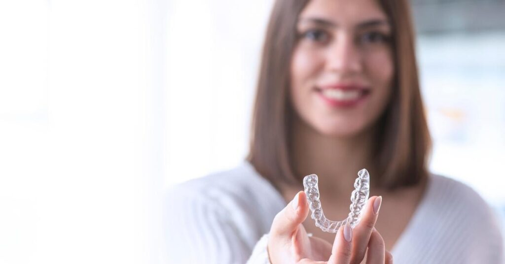 woman holds invisalign